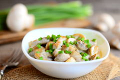 Tranches frites de champignons avec de la sauce à crème sure et de jeunes oignons verts dans une cuvette Recette délicieuse de ch Image stock