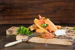 Tranches frites de patate douce, igname crue avec des pepers piments, tomates et verdure sur un fond foncé de conseil en bois images libres de droits