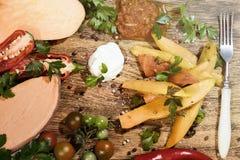 Tranches frites de patate douce, igname crue avec des pepers piments, tomates et verdure sur un fond foncé de conseil en bois photos libres de droits