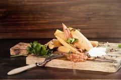 Tranches frites de patate douce, igname crue avec des pepers piments, tomates et verdure sur un fond foncé de conseil en bois image stock