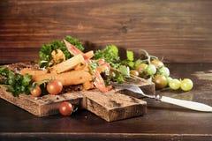 Tranches frites de patate douce, igname crue avec des pepers piments, tomates et verdure sur un fond foncé de conseil en bois photos stock