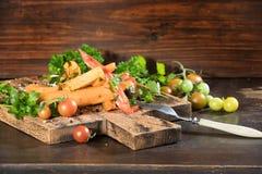 Tranches frites de patate douce, igname crue avec des pepers piments, tomates et verdure sur un fond foncé de conseil en bois photographie stock