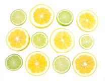 Tranches jaunes et vertes de citron et de chaux sur le fond blanc Images libres de droits