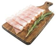 Tranches minces de prosciutto avec le romarin sur la planche à découper en bois, fond de vintage Images stock