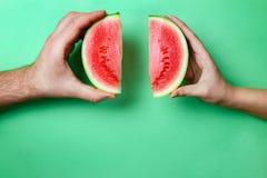Tranches Mini Watermelon dans des mains femelles et masculines avec l'espace vert de copie Image libre de droits