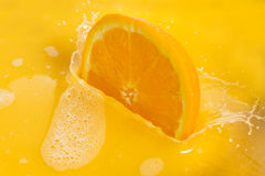 Tranches oranges éclaboussant dans le jus d'orange sur le fond blanc image stock