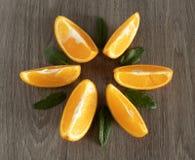 Tranches oranges avec les feuilles en bon ?tat sur une surface texturis?e en bois photographie stock libre de droits