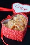 Tranches oranges glacées dans un couvercle rouge en forme de coeur d'une boîte avec le ruban rouge sur un fond noir Jour du ` s d Photos stock