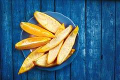 Tranches oranges sur le conseil en bois bleu Photos libres de droits