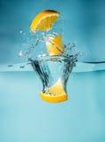 Tranches oranges tombant dans le plan rapproché de l'eau, macro, l'eau d'éclaboussure, bulles photographie stock libre de droits