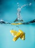 Tranches oranges tombant dans le plan rapproché de l'eau, macro, l'eau d'éclaboussure, bulles photos libres de droits