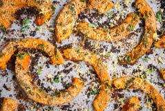 Tranches rôties de potiron avec des herbes sur le papier de cuisson closeup Photo libre de droits