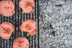 Tranches rôties de saucisse sur un gril, vue supérieure, récréation extérieure, pique-nique Photos stock
