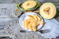 Tranches rondes de melon sur une planche à découper Image libre de droits
