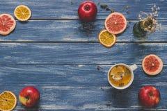 Tranches sèches d'agrume avec la tasse de thé et de pommes sur la table en bois bleue, vue supérieure Copiez l'espace Image stock