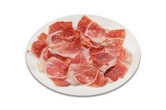 tranches Sec-traitées de jambon sur l'ombre blanche de plat et le fond blanc Photo libre de droits