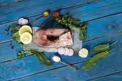 Trancio di pesce crudo con le spezie, le erbe ed il limone su un BAC di legno blu Fotografia Stock Libera da Diritti