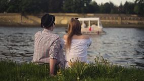 Trandy couple talking by the river. Holidays, vacation, love and people concept - happy teenage couple sitting by river Visla. At summer. Couple on dating stock video footage