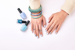Trandy female manicure with blue bracelets on a white background. Different nail polishes. Blue manicure and correctly selected bijouterie stock images