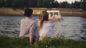 Trandy par som talar vid floden Ferie-, semester-, förälskelse- och folkbegrepp - lyckligt tonårs- parsammanträde vid floden Visl lager videofilmer