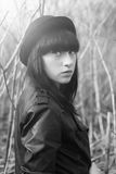 Trandy style portrait of young  girl in fashionable hat and leather jacket. Black and white portrait outdoor Stock Images