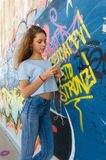 Trandy teenager watching a smartphone. A teenager is leaning against a graffiti wall watching her smartphone after school Stock Images