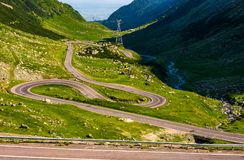 Tranfagarasan road in Romanian mountains. Transfagarasan road in Romanian mountains. winding serpentine among the grassy hills on a sunny morning royalty free stock images