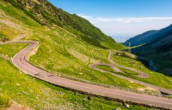 Tranfagarasan road in Romanian mountains. Transfagarasan road in Romanian mountains. winding serpentine among the grassy hills on a sunny morning stock photos