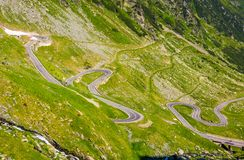 Tranfagarasan road in Romanian mountains. Transfagarasan road in Romanian mountains. winding serpentine among the grassy hills on a sunny morning Stock Image