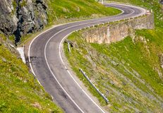 Tranfagarasan road in Romanian mountains. Transfagarasan road in Romanian mountains. winding serpentine among the grassy hills on a sunny morning Royalty Free Stock Photos