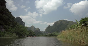 Trang an bai in Hanoi, Vietnam on a scenic river sailing boat with tourists. Seen trees and mountains stock footage