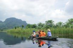 Trang, Ninh Binh, Вьетнам - 13,2014 -го сентябрь: Посетители посещают красивые реку и гору от шлюпки вдоль реки стоковое фото rf