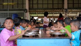 Children enjoy having lunch in cafeteria stock video footage