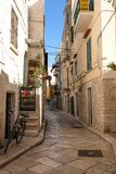 Street scene with bicycle in the foreground, in the Jewish Quarter of the historic medieval town of Trani in Puglia, Italy. Trani, Puglia, Italy. Street scene royalty free stock photos
