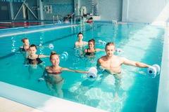 Traninig de los aeróbicos de la aguamarina de las mujeres con pesas de gimnasia Imagenes de archivo