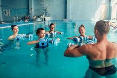 Traninig de los aeróbicos de la aguamarina de las mujeres con pesas de gimnasia Imagen de archivo