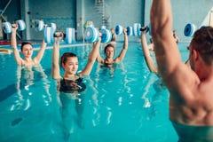 Traninig de los aeróbicos de la aguamarina de las mujeres con pesas de gimnasia Foto de archivo libre de regalías