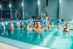 Traninig di aerobica dell'acqua del gruppo in stagno dell'interno Fotografia Stock