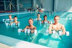 Traninig di aerobica dell'acqua delle donne con le teste di legno Immagini Stock