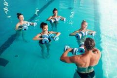 Traninig di aerobica dell'acqua delle donne con le teste di legno Fotografia Stock Libera da Diritti