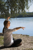 Tranquil. Beautiful girl doing yoga exercise on the river bank Royalty Free Stock Images