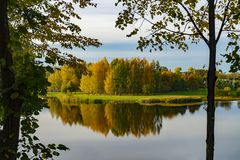 Tranquil autumn lake with colorful reflections. Tranquil autumn lake with reflections of trees with colorful foliage viewed past a trees branches and leaves stock photography