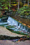 Tranquil Autumn Stream with Waterfall Royalty Free Stock Photography