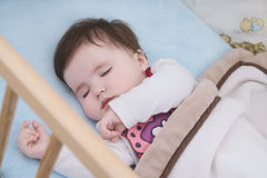 Tranquil baby. Close up on the face of sleeping child in her cot Royalty Free Stock Photo