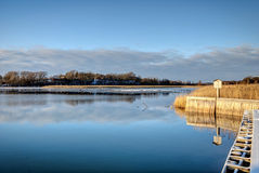Tranquil bay with dry grass and pier in winter time Royalty Free Stock Photography