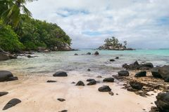 Tranquil bay with white sand, overcast skies, granite stones and turquoise sea at Fairyland Beach, Seychelles Africa. Tranquil bay with white sand, granite royalty free stock photos