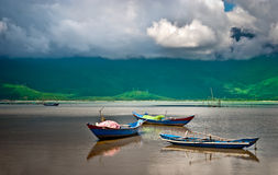 Tranquil bay with wooden boats in Vietnam. A beautiful landscape with three wooden boats reflecting in the tranquil waters of a bay under a dramatic sky. The Stock Photo