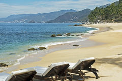 Tranquil beach with lounge chairs royalty free stock photos
