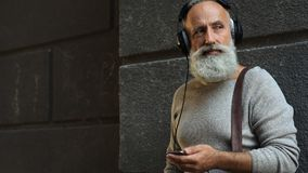 Tranquil bearded guy looking at phone while listening to music