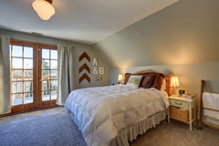 Tranquil bedroom with sloped ceiling and doors to nice deck. Stock Images